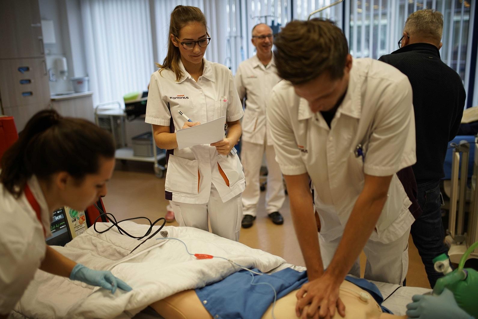 leerling verpleegkunidge oefent reanimatie, andere leerlingen kijken toe